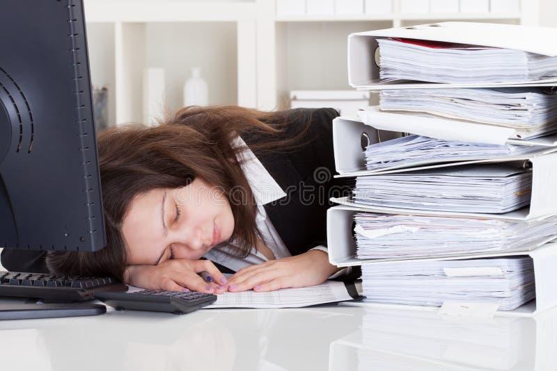 Усиленная женщина спать в офисе стоковое фото
