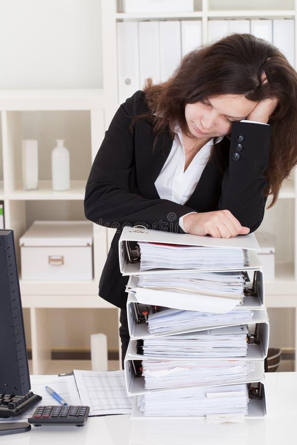 Усиленная женщина спать в офисе стоковое фото rf