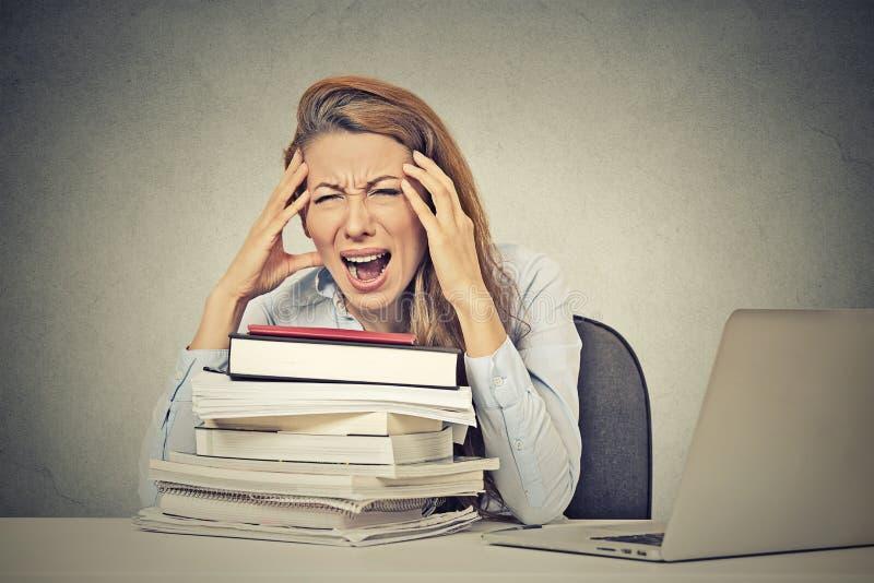 Усиленная кричащая женщина сидя на столе с компьютером книг стоковое изображение