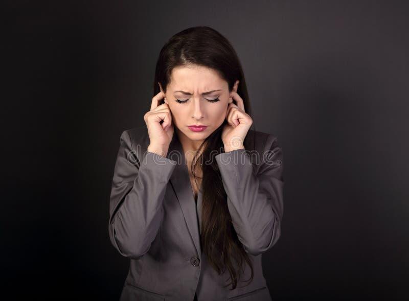 Усиленная унылая бизнес-леди в сером костюме закрыла ее уши ребро стоковые фото