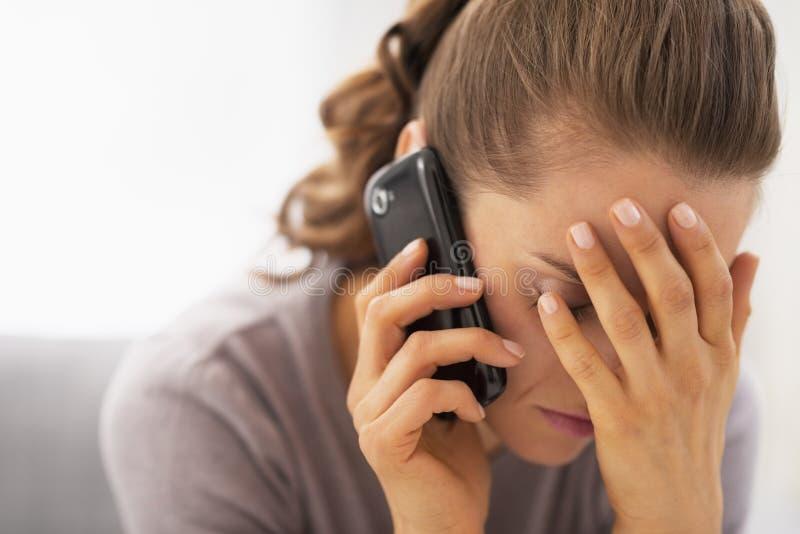 Усиленный мобильный телефон молодой женщины говоря стоковые фотографии rf