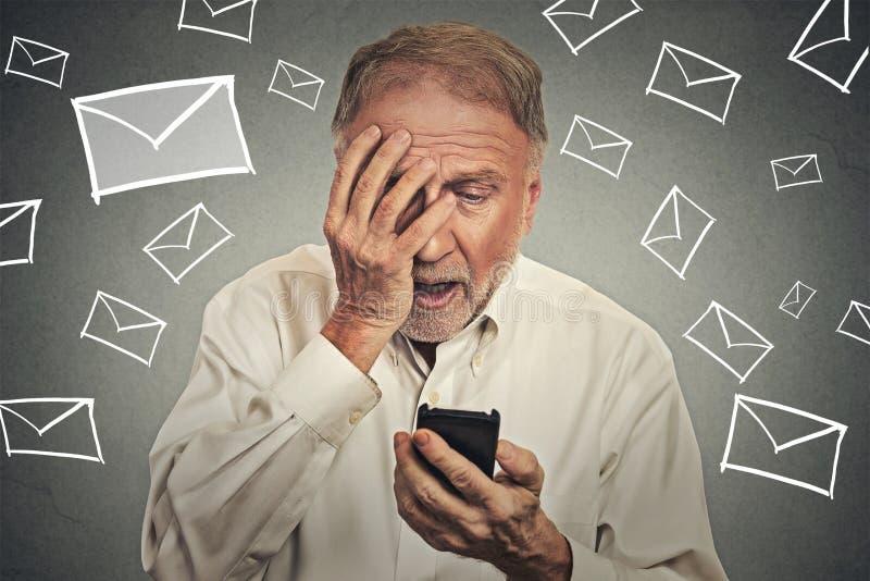 Усиленный человек держа мобильный телефон сотрясенный при полученное сообщение стоковые фото