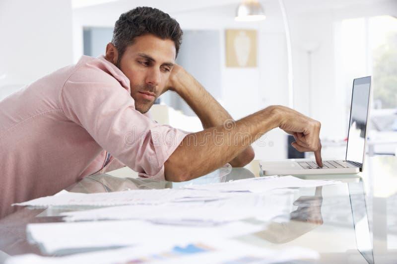 Усиленный человек работая на компьтер-книжке в домашнем офисе стоковая фотография