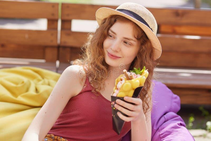 Услаженная курчавая с волосами модель лежа на погремушках на кафе, смотрящ в сторону, держащ еду в одной руке, нося соломенную шл стоковая фотография