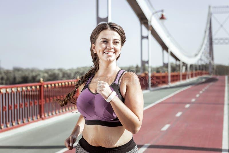 Услаженная славная женщина jogging на мосте стоковое фото