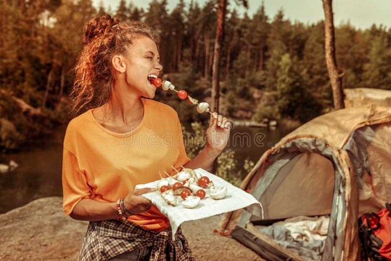 Услаженная счастливая женщина пробуя вкусный томат стоковые изображения rf