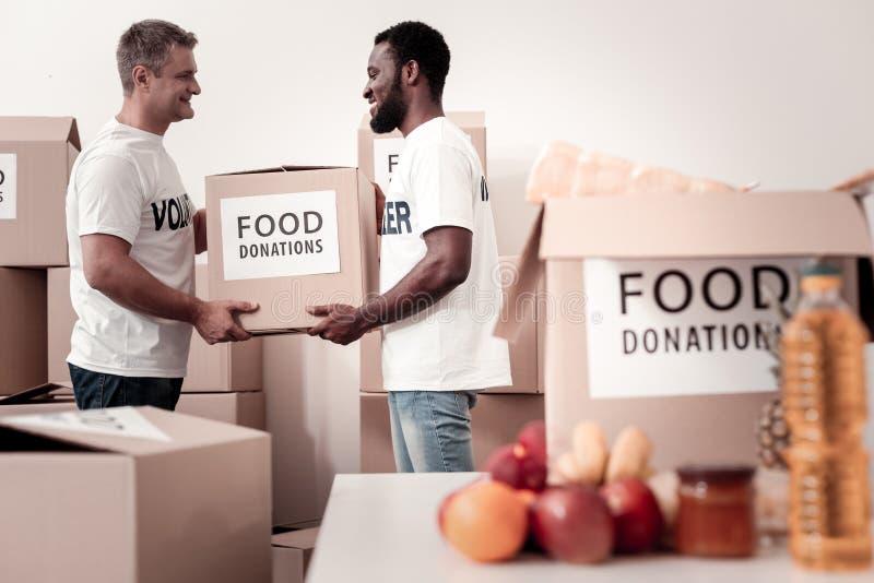 Услаженные волонтеры держа большой пакет стоковая фотография rf