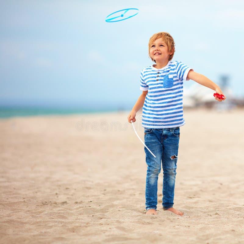 Услаженный милый молодой мальчик, ребенк имея потеху на песчаном пляже, играя игры досуга с игрушкой пропеллера стоковые фотографии rf