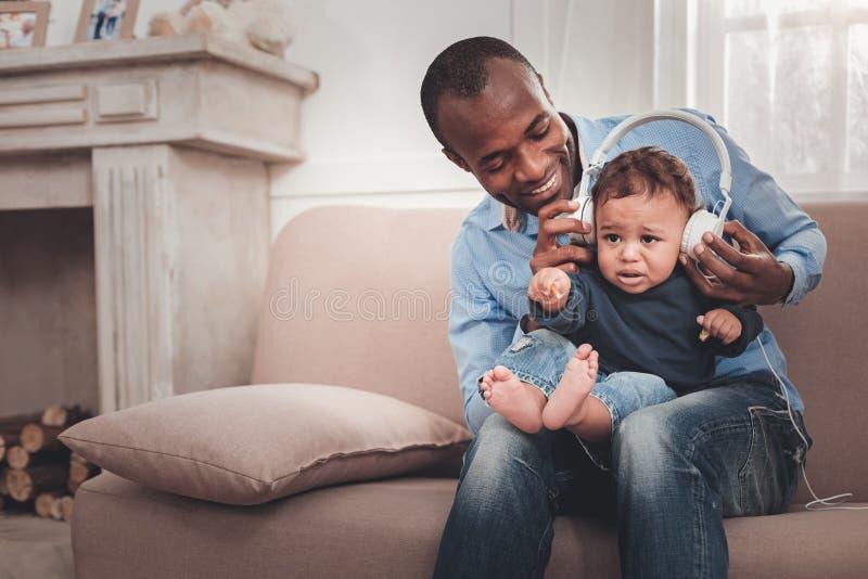 Услаженный положительный человек держа его младенца стоковые фотографии rf