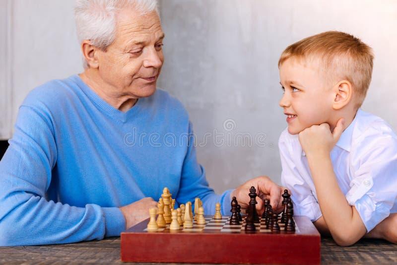 Услаженный славный мальчик играя шахмат стоковая фотография rf