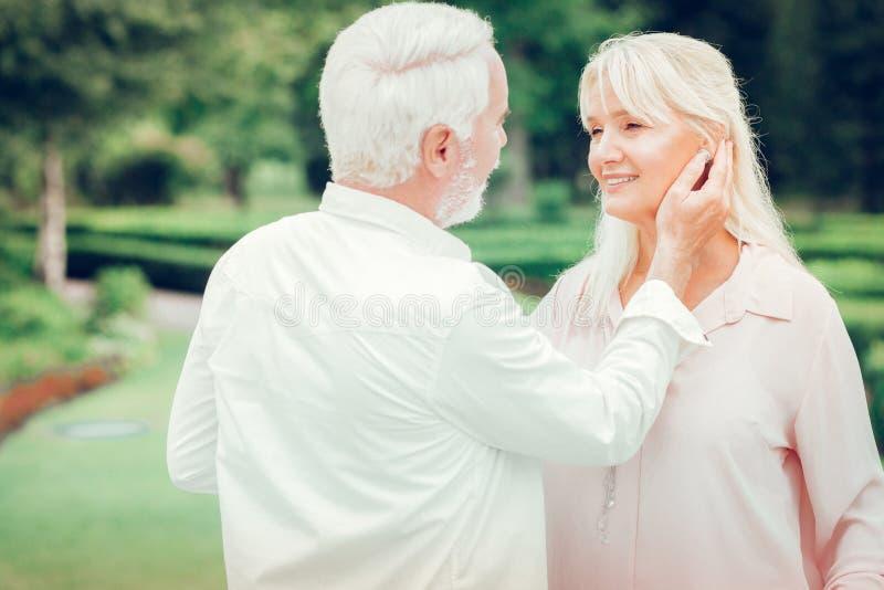 Услаженный славный человек касаясь его щеке жен стоковые фото