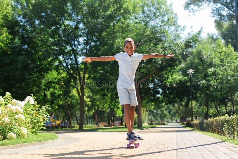 Услаженный счастливый активный мальчик наслаждаясь катанием скейтборда стоковые изображения rf
