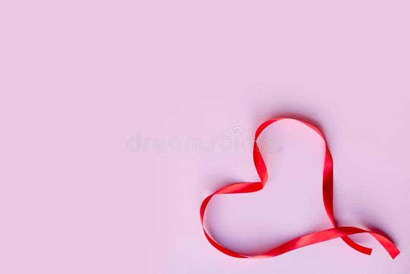 Услышанная красная лента шелка, на розовой предпосылке Мать, женщины, свадьба, счастливая концепция дня Святого Валентина, 14-ое  стоковое изображение