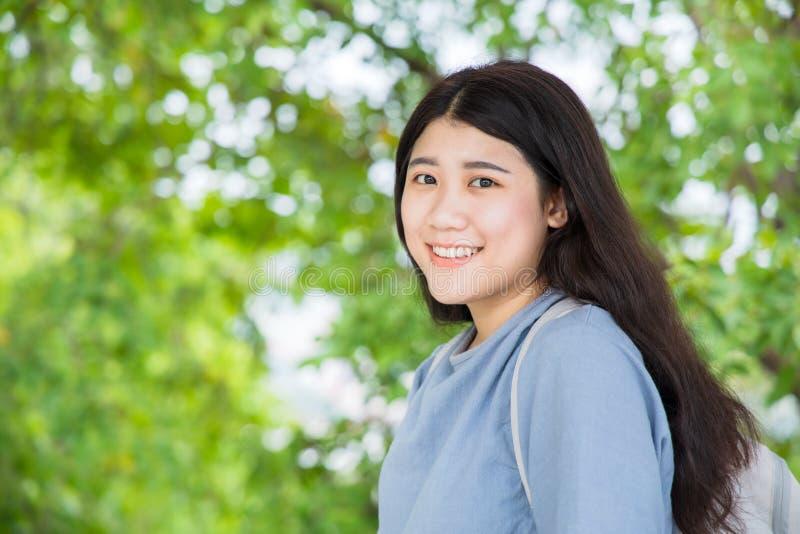 Усмехаться азиатской девушки предназначенный для подростков милый здоровый на зеленой предпосылке природы с космосом стоковые изображения rf