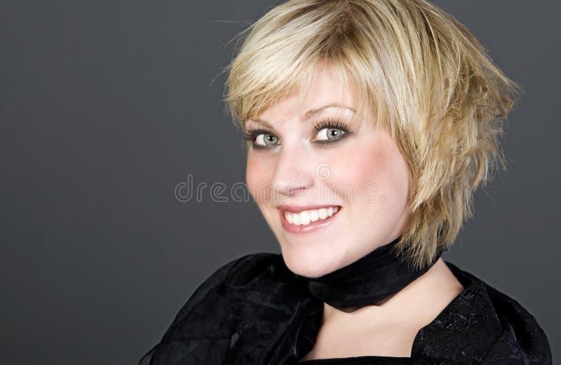 усмехаться белокурой девушки камеры с волосами стоковое изображение