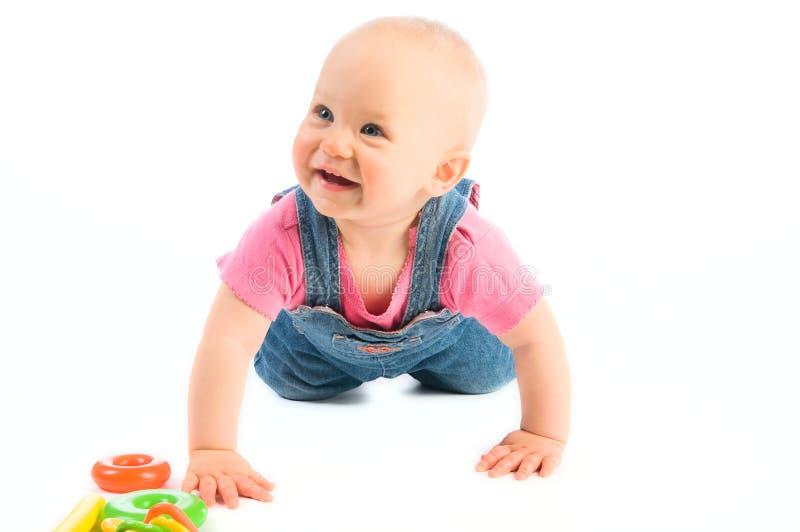 усмехаться девушки младенца вползая стоковое изображение