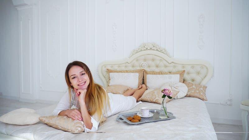 Усмехаться девушки модельный на камере лежа на кровати в яркой спальне стоковое фото rf