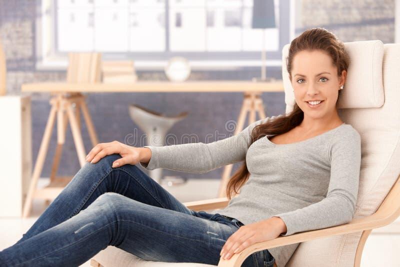 усмехаться дома девушки кресла милый ослабляя стоковое фото
