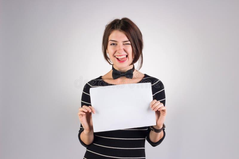 фото с белым листом бумаги в руках цветы окружены темно-зелеными