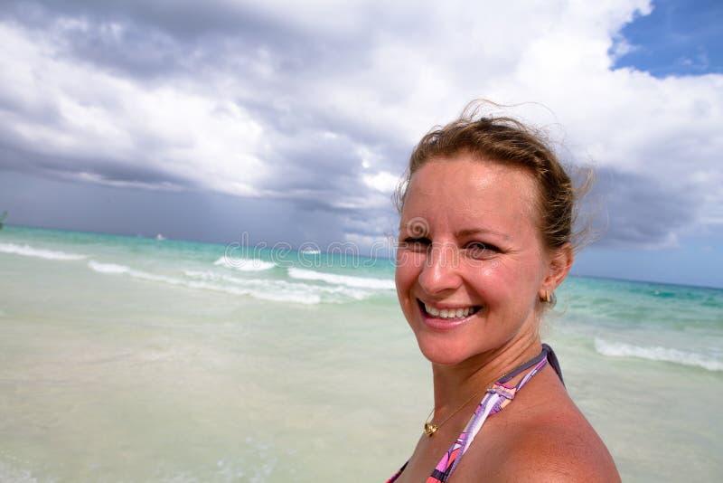 Усмехаться естественно на пляже стоковые изображения