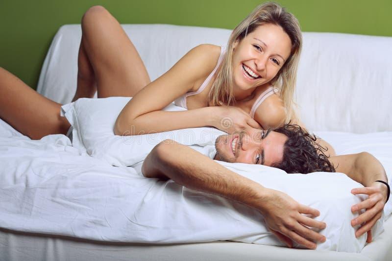 Усмехаться и радостные пары шутя в кровати стоковые фотографии rf