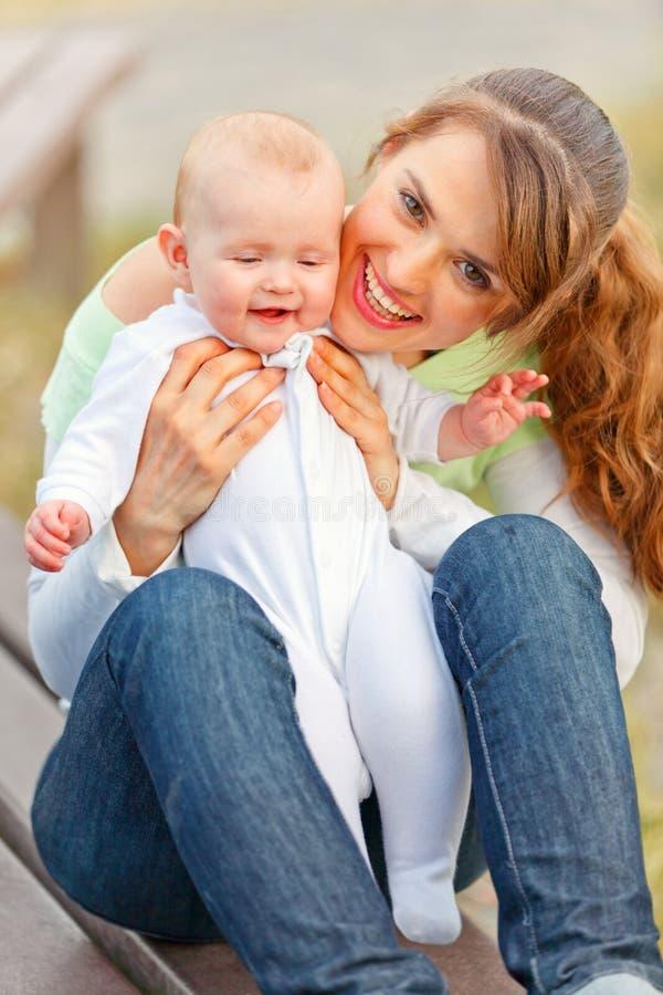 усмехаться мати удерживания прелестного ребёнка счастливый стоковое изображение rf
