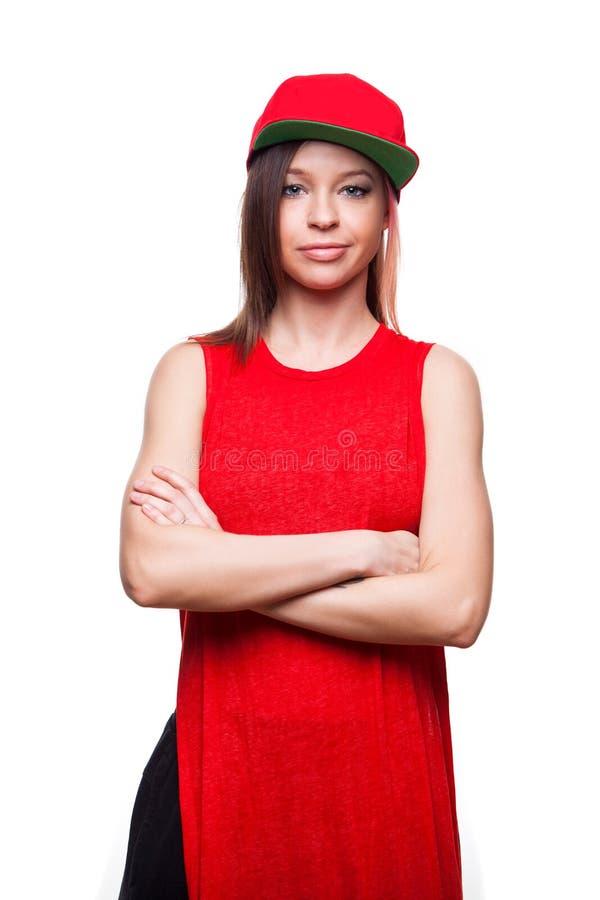 Усмехаться молодой женщины, смотря камеру Красная бейсбольная кепка стоковые фото