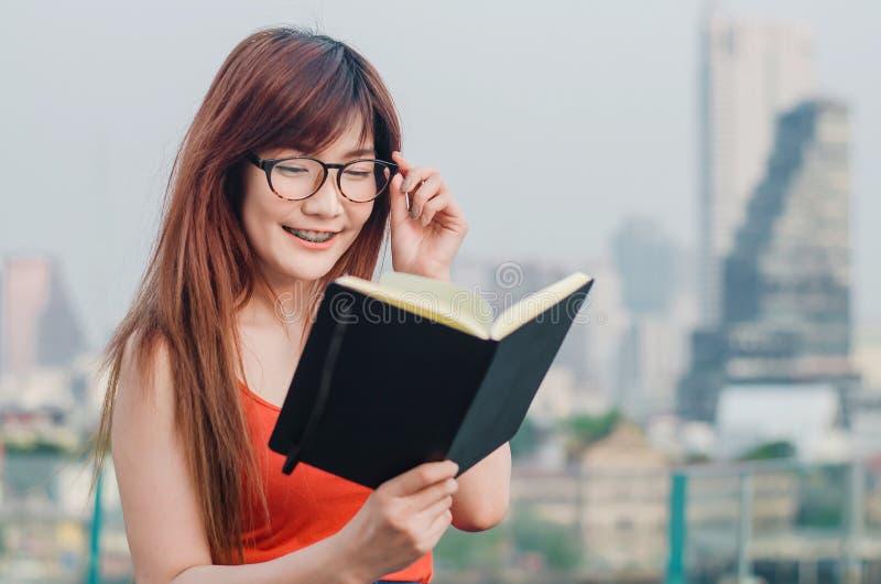 Усмехаться молодым красивым азиатским женщинам в стеклах читает книгу в городе лета стоковые изображения rf