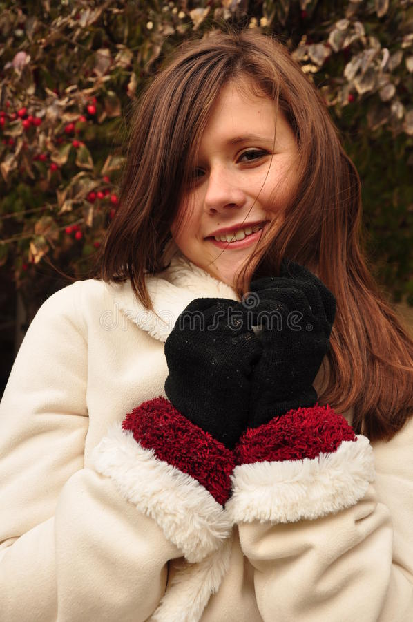 Усмехаться предназначенный для подростков в белом пальто стоковое фото rf