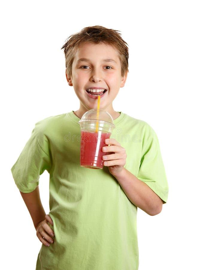 усмехаться сока удерживания свежих фруктов мальчика стоковая фотография rf