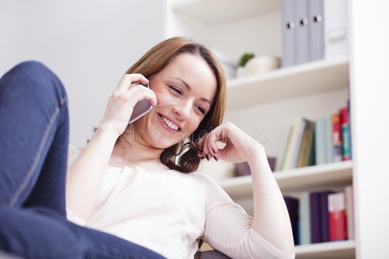Усмехаться счастливой коричневой с волосами девушки сидя на софе стоковые фотографии rf