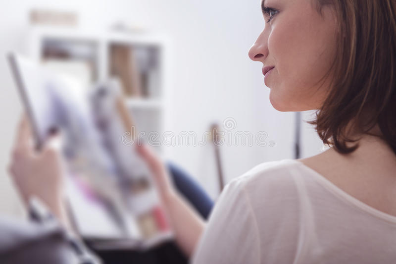 Усмехаться счастливой коричневой с волосами девушки сидя на софе стоковые фото