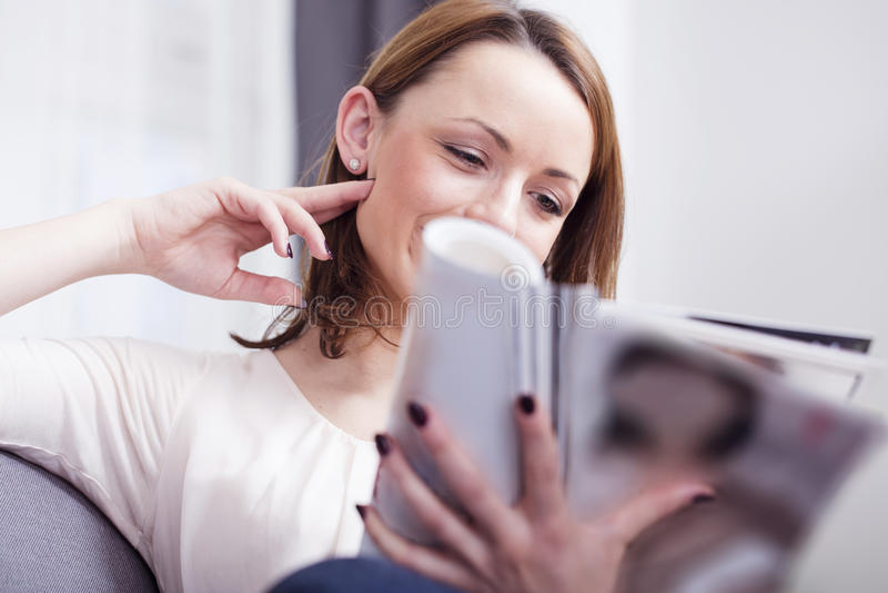Усмехаться счастливой коричневой с волосами девушки сидя на софе стоковая фотография rf