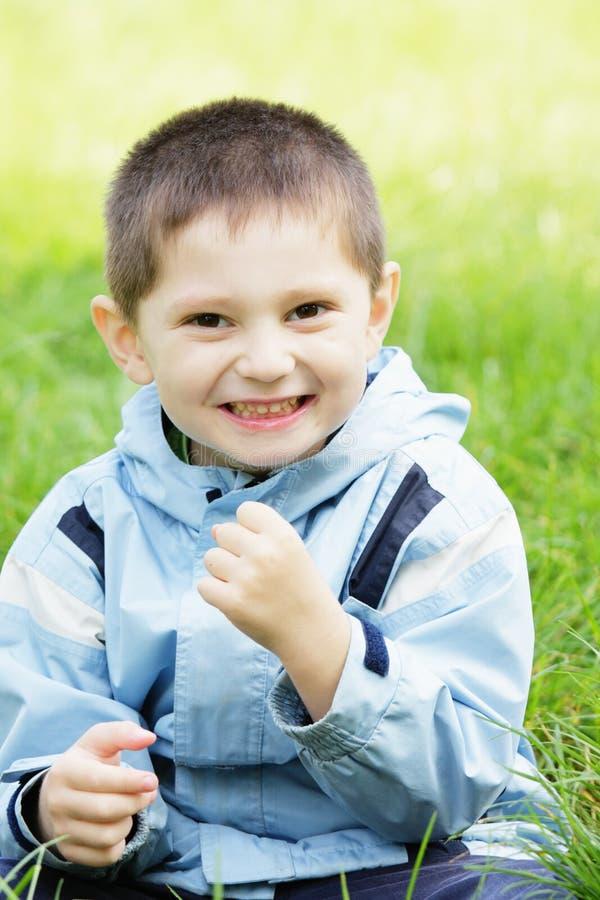 усмехаться травы мальчика стоковое изображение