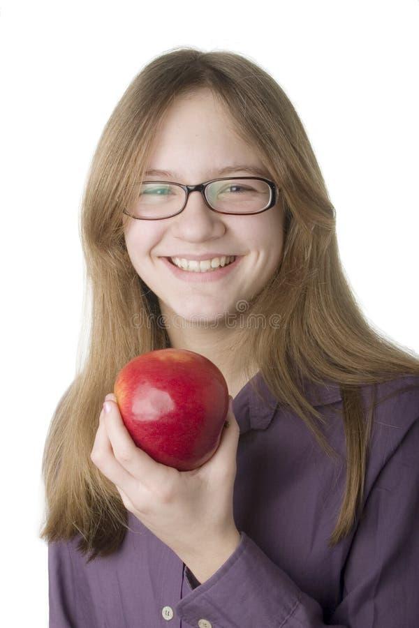усмехаться удерживания девушки яблока стоковое фото