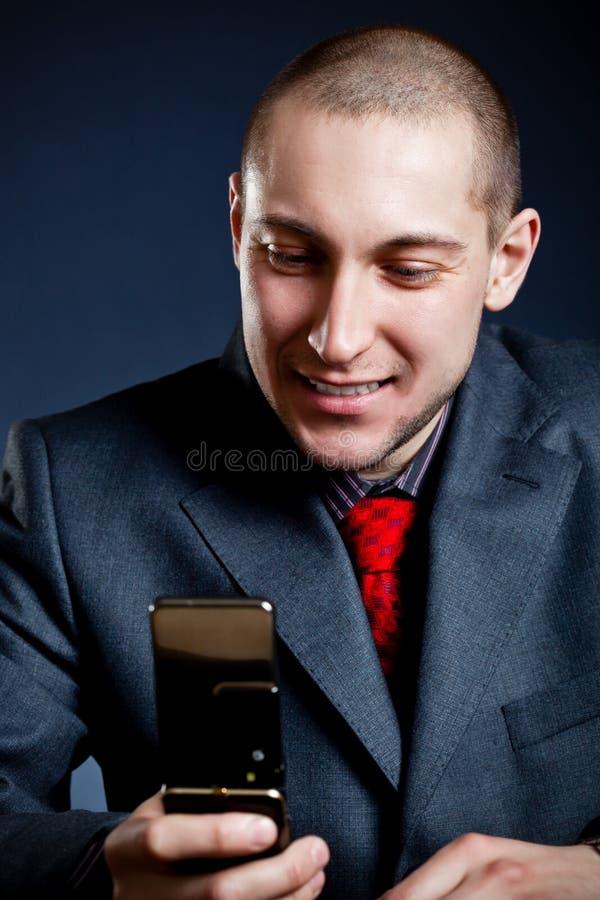усмехаться чтения сообщения бизнесмена стоковые фото