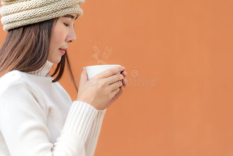 Усмехающся ваши азиатские женщины вручите держать белую чашку кофе на погоде зимы, полный фон цвета стоковые изображения rf
