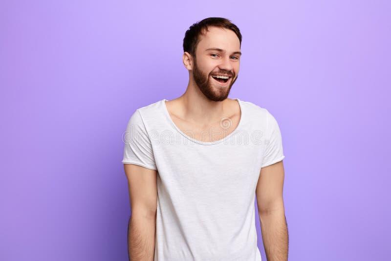 Усмехающся, смеясь молодой человек с белой футболкой смотря камеру стоковые изображения rf