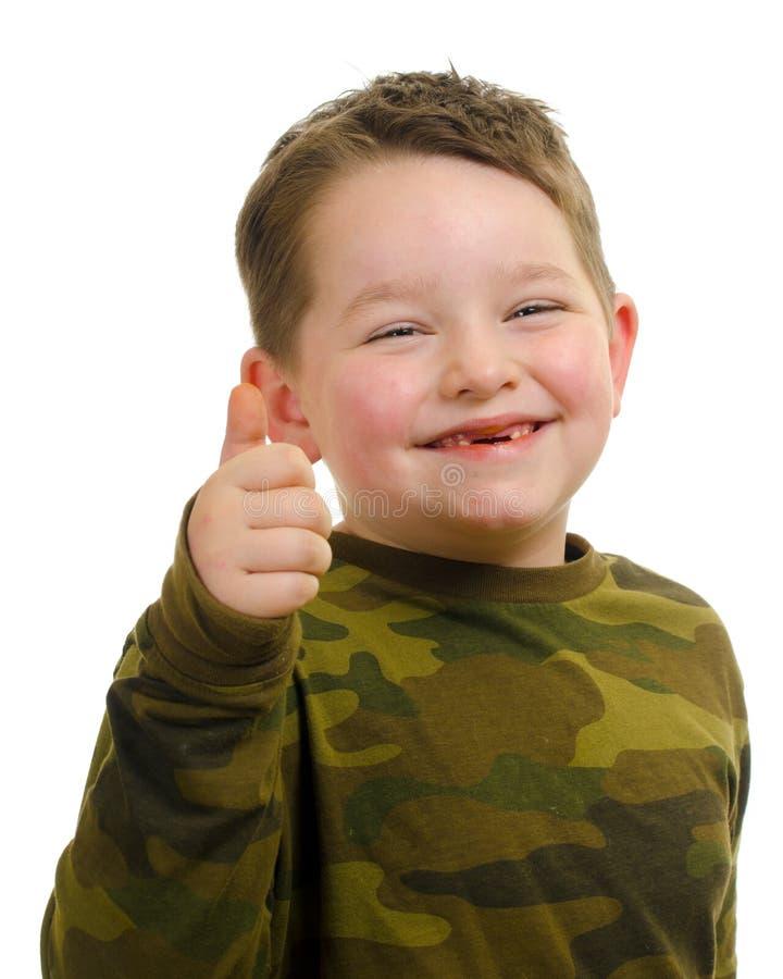 Усмехающся, счастливый мальчик держа его большой палец руки вверх стоковые фото