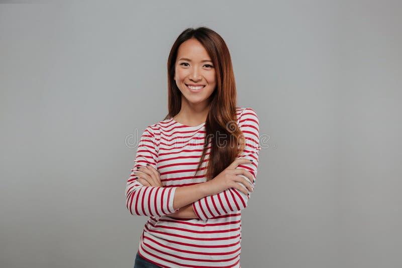 Усмехаясь азиатская женщина в свитере представляя с пересеченными оружиями стоковое фото rf