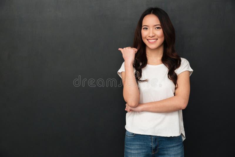 Усмехаясь азиатская женщина в футболке указывая прочь стоковая фотография
