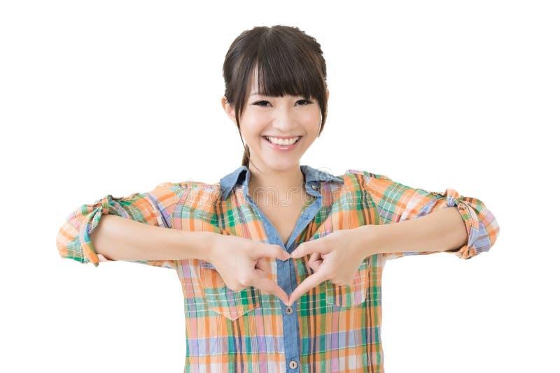 Усмехаясь азиатская женщина делает форму сердца стоковое изображение