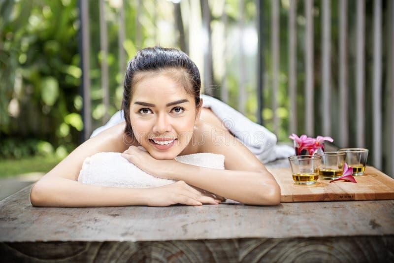 Усмехаясь азиатская женщина наслаждаясь заботой кожи стоковые изображения rf