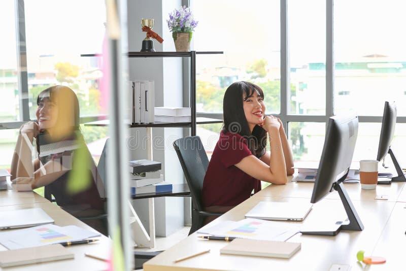 Усмехаясь азиатская женщина ослабляя в офисе стоковое фото rf