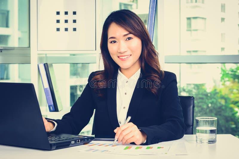 Усмехаясь азиатская коммерсантка работая в офисе стоковое фото rf