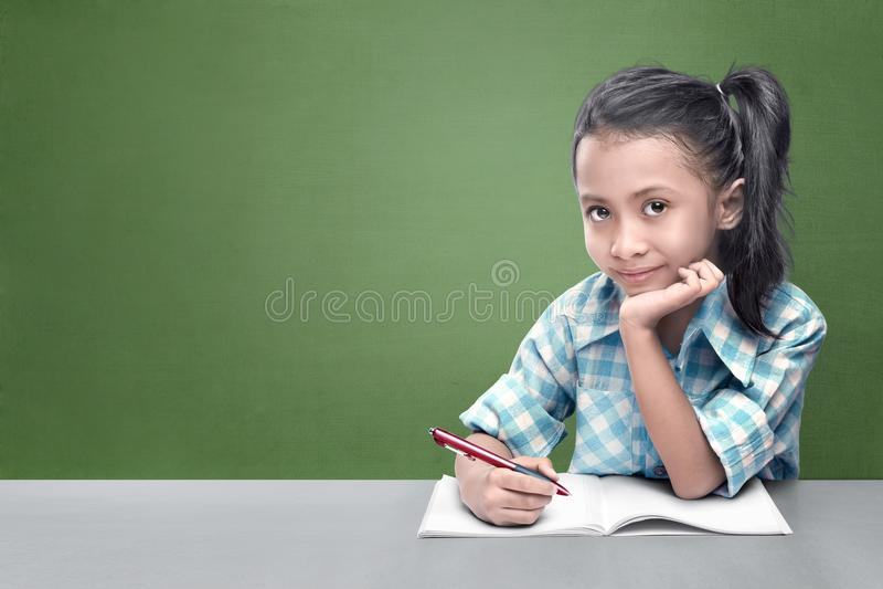 Усмехаясь азиатская маленькая девочка делая ее домашнюю работу стоковые изображения