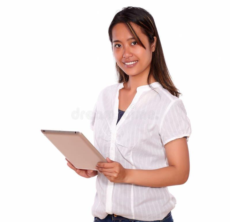 Усмехаясь азиатская молодая женщина используя ее ПК таблетки стоковое изображение