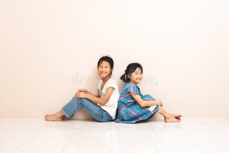 Усмехаясь азиатские братья сидеть и касаться один другого с их задними частями Прекрасные задушевные эмоции от детства стоковые фотографии rf