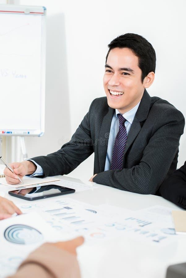 Усмехаясь азиатский бизнесмен на встрече стоковые изображения