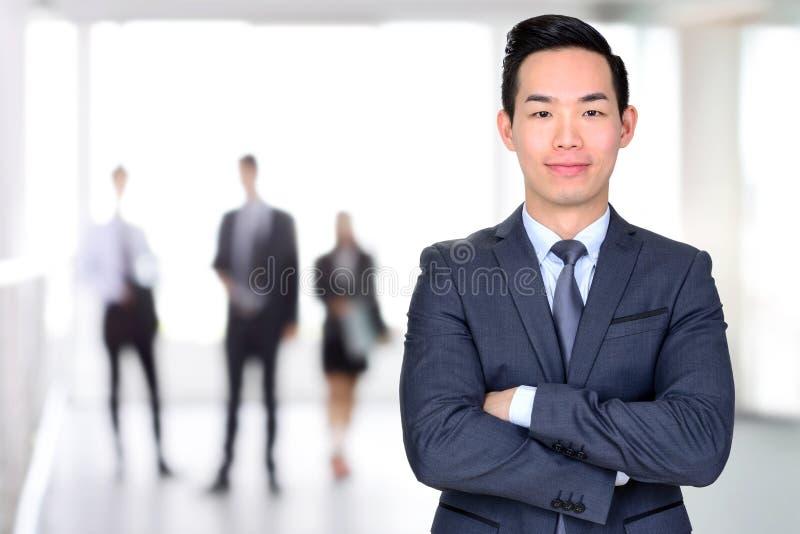 Усмехаясь азиатский бизнесмен пересекая его оружия стоковые изображения